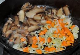 В другой сковороде, разогретой на среднем огне, на небольшом количестве масла пассеровать полукольца лука с нарезанной морковкой 5-7 минут, после чего заложитьвu00a0 сковороду и ломтики грибов. Потушить 3-4 минуты.