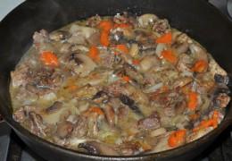 К говядине, когда она практически готова, добавить заправку с грибами из второй сковороды. Положить томатную пасту, посыпать мукой, перемешать.