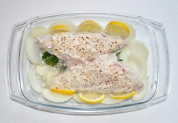 Перед отправкой в духовку нарезать кружками лук, разложить вокруг рыбы, добавить несколько тонких ломтиков лимона. Посыпать перцем. Разложить несколько мелких кусочков сливочного масла.